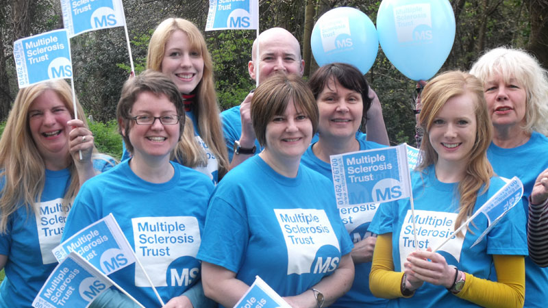 Group of MS Trust supporters in MS Trust t-shirts holding flags and balloons