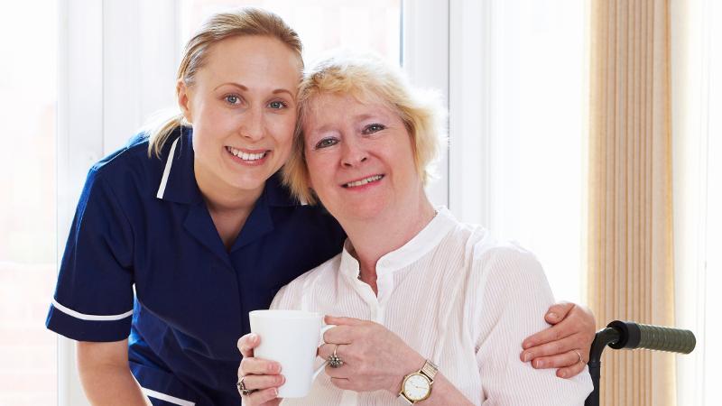 Nurse hugging patient in wheelchair