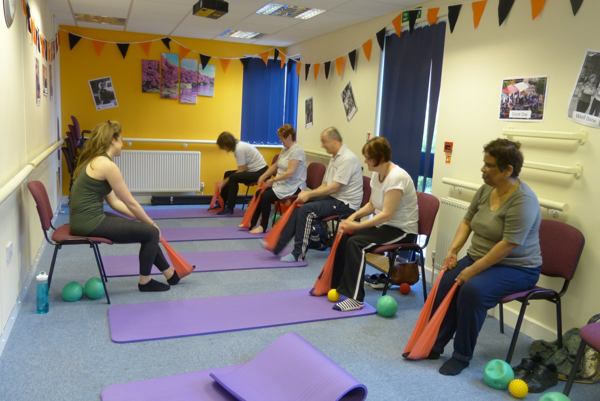 Group of people sitting down doing pilates