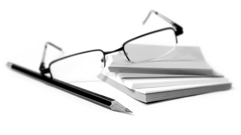 Black and white image of glasses pencil and stack of post it notes