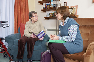 MS specialist nurse sitting with patient in home