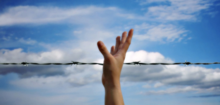 Hand reaching up in the sky in front of barbed wires