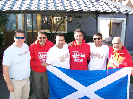 Rick with a group of people and a Scottish flag