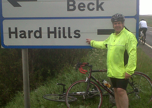 Rick pointing at a sign that says 'Hard Hills'