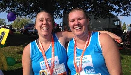 Two runners in MS Trust vests