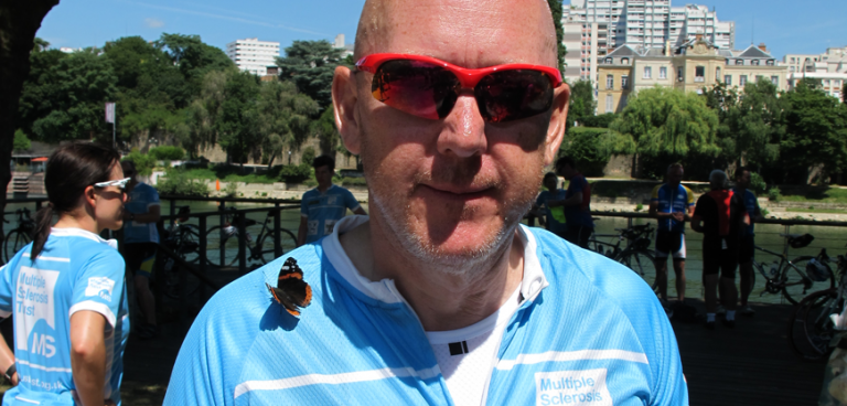 Dave in his MS Trust top with a butterfly on his shoulder