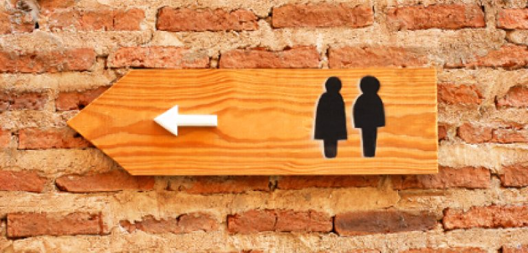 Toilet sign on brick wall