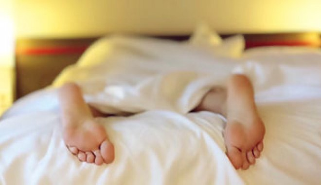 Person sleeping in bed with feet poking out