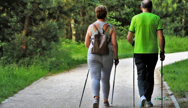 Couple walking with trekking poles in  the woods
