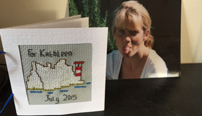 Photo of Kathleen with a cross-stitched card of the Isle of Wight