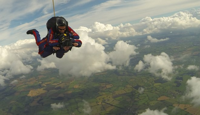 Jenifer skydiving over fields