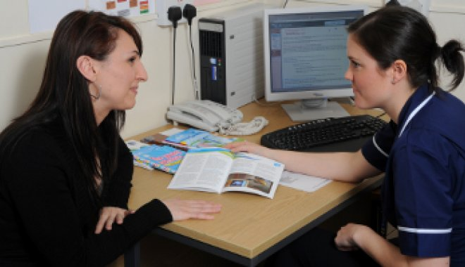 Patient sitting at desk with her health professional for an appointment