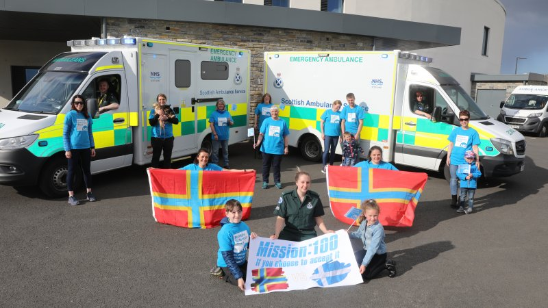 Supporters of all ages in blue MS Trust t-shirts stand in front of two NHS ambulances. Two people hold the flag of Orkney in the forefront.