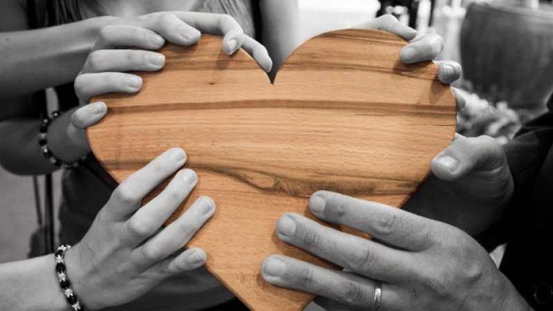 Hands holding a wooden heart