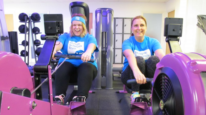 Two people taking part in indoor rowing for Miles for MS