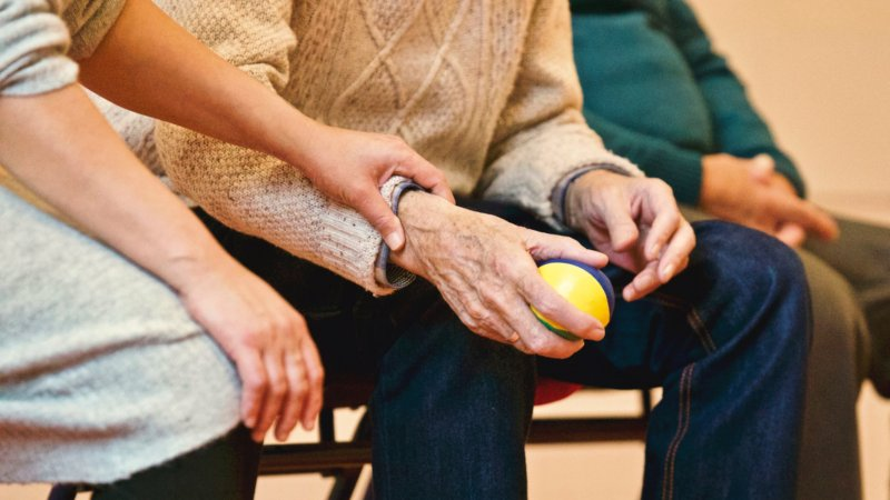 adults hold hands and a ball