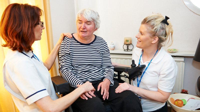 Patient in wheelchair with two nurses