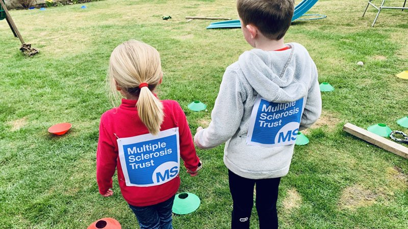 Two children fundraising in their garden for the MS Trust