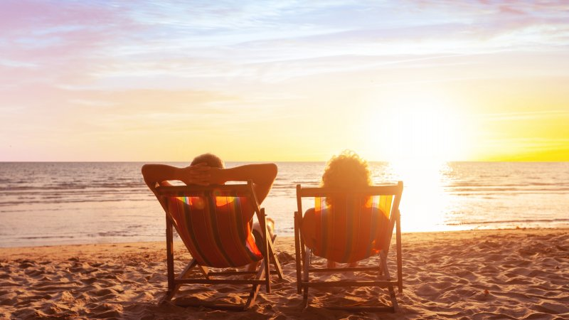 Two people sit side by side in deckchairs on a sunny beach