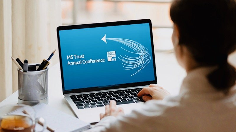 Female sat at a desk using a laptop that says 'MS Trust Conference' on the screen