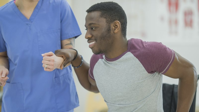 Image of nurse assisting young man