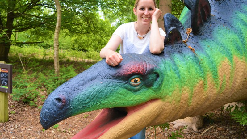 Image shows the author, Emily, smiling while leaning against a large, model dinosaur.
