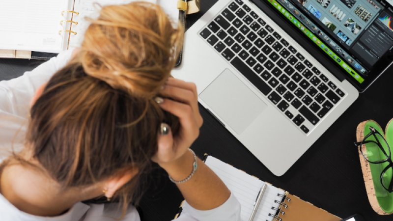Stressed woman sitting at desk with head in hands