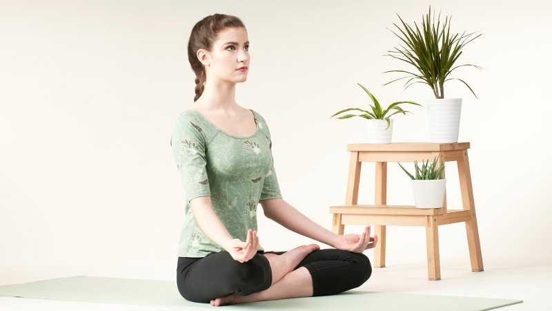 Woman sitting on floor next to plant in yoga pose