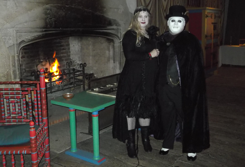 Melissa and Peter in fancy dress in front of a fireplace